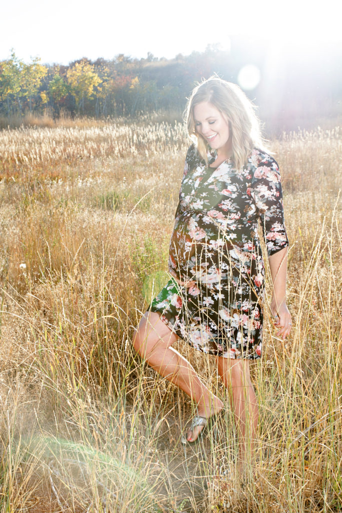 maternity photoshoot in a field with sunflare